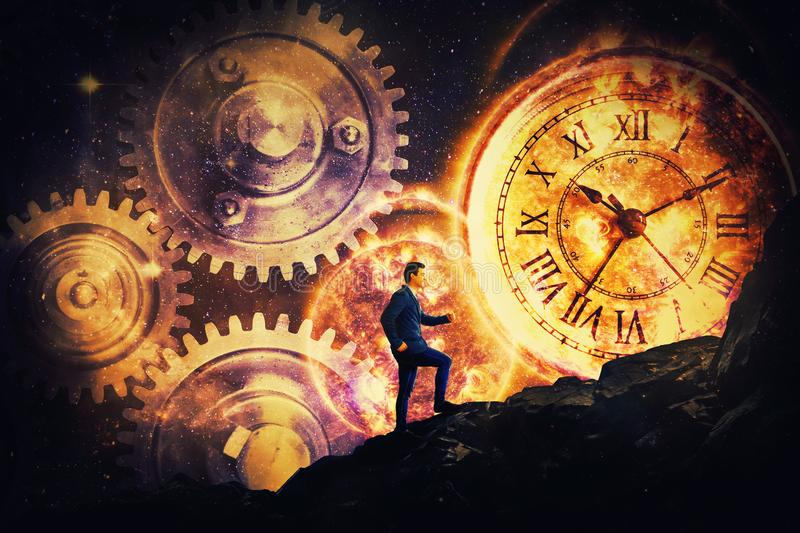 It`s a matter of time. Surreal view as a businessman climbing a tall mountain over a night starry sky background. Mystic clock and gears as the matter of time in royalty free stock images