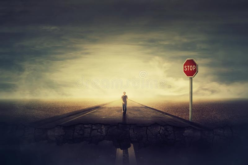 Surreal view as man walks a crushing asphalt road as STOP red sign warns of danger. Deep hole in the ground, chasm as broken way royalty free stock photography