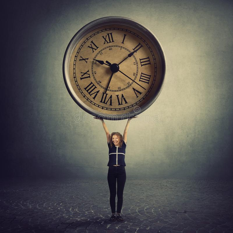 Surreal view as a tiny girl teenager lifting a huge clock over head. Student time management concept. Educational process hours, stock photo
