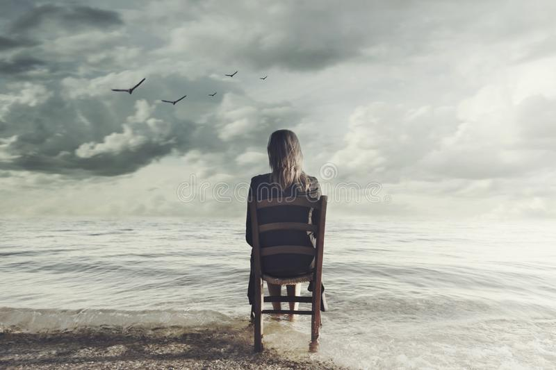 Surreal woman looks at the infinite sitting on a chair inside the sea royalty free stock photography