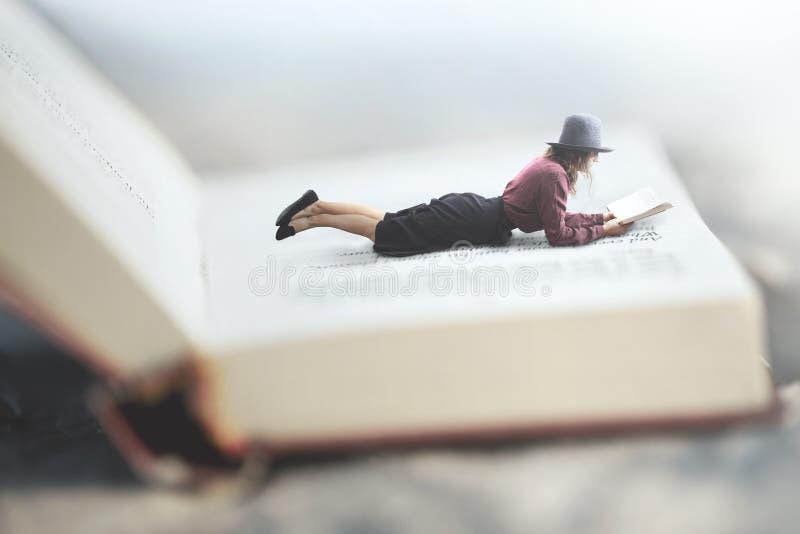 Surreale Situation einer Frau, die ihr Buch liegt auf einem riesigen Buch liest lizenzfreie stockfotografie