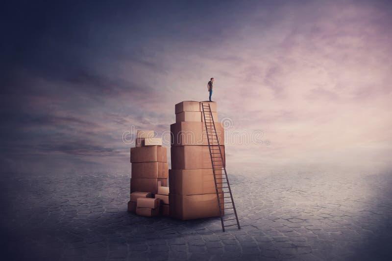 Surreale Szene als winziger Mann Wanderer auf einem Stapel Kartonboxen, halten Hand zu Stirn Blick auf den Horizont lizenzfreies stockfoto
