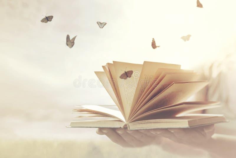 Surrealer Moment der Freiheit für die Schmetterlinge, die aus ein offenes Buch herauskommen stockbild