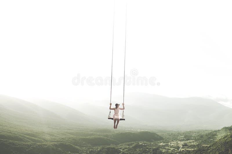 Surrealer Moment einer Frau, die Spaß auf einem Schwingen hängt vom Himmel hat stockfoto