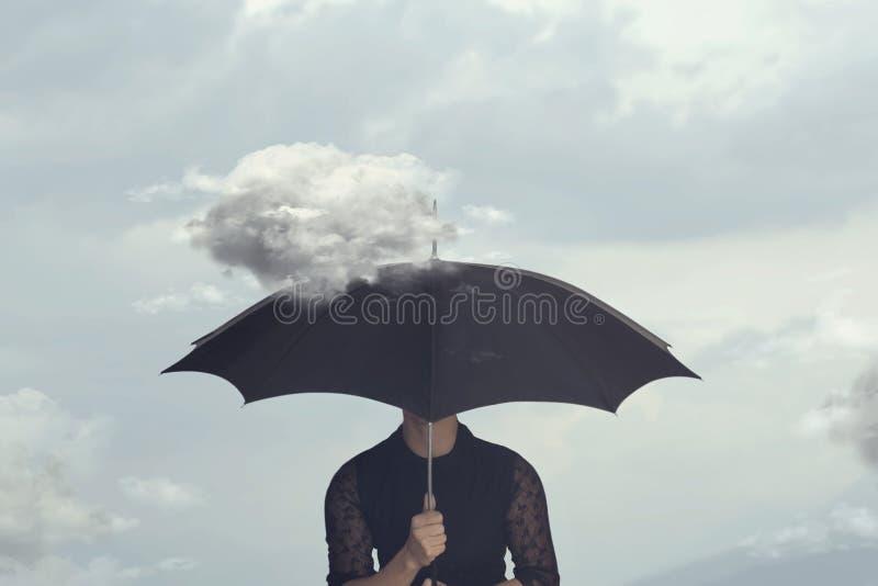 Surrealer Moment einer Frau, die unter dem Regenschirm von einer kleinen Wolke sich versteckt, die sie jagt lizenzfreie stockbilder