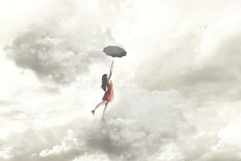 Surrealer Moment eines Fliegens der eleganten Frau mitten in den Wolken, die an ihrem Regenschirm hängen lizenzfreies stockfoto