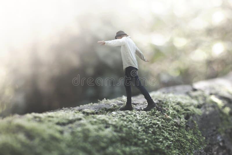 Surrealer Moment eines Frauengehens ausgeglichen auf einem riesigen Baumstamm im Wald stockfotografie