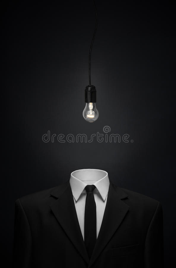 Surrealism and business theme: Burning glass bulb instead of a head man in a black suit on a dark background in the studio. Surrealism and business theme royalty free stock photography