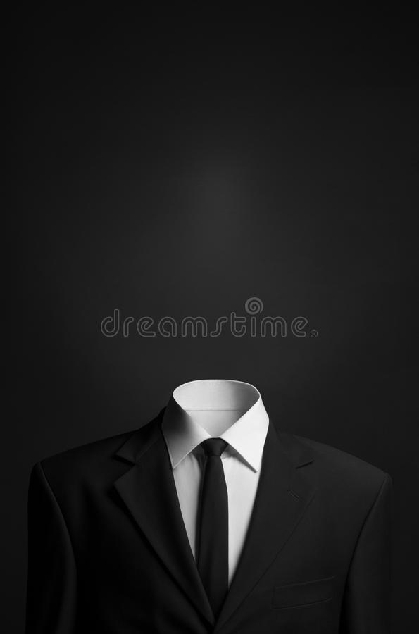 Surrealism and business theme: a man without a head in a black suit on a dark background in the studio. Surrealism and business theme: a man without a head in a stock photo