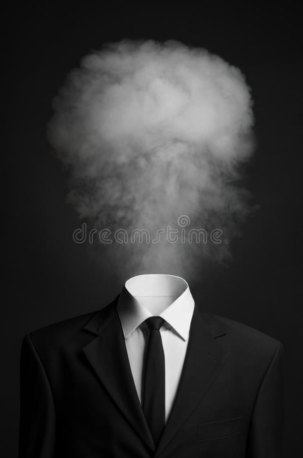Surrealism and business topic: the smoke instead of a head man in a black suit on a dark background in the studio. Surrealism and business topic: the smoke stock photography
