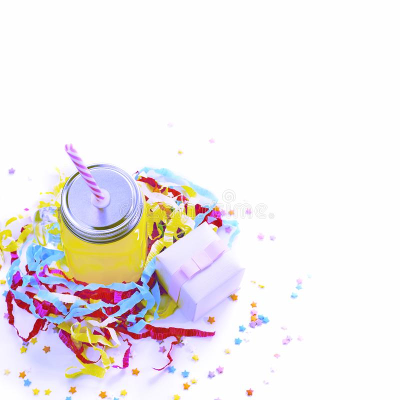 Surrealism Decorative composition festive exotic cocktail on white background box with confetti gift satin ribbon. stock photos