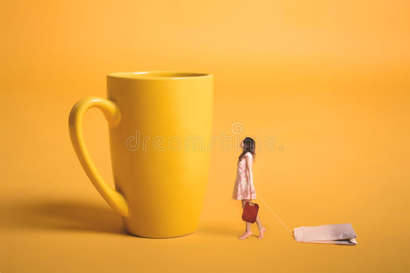 Surrealism design. Girl holding a tea bag in his hand. Miniature people. Yellow empty cup on a yellow background. Young girl makes tea stock photos