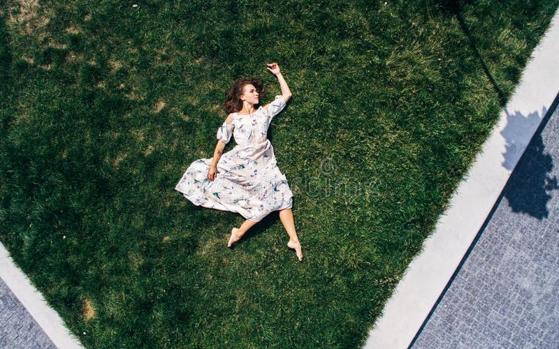 Surrealism. The girl lies on a green lawn in a dress. Aerial view. Surrealism. Red-haired girl lies barefoot on a green lawn in a dress. Aerial view royalty free stock photo