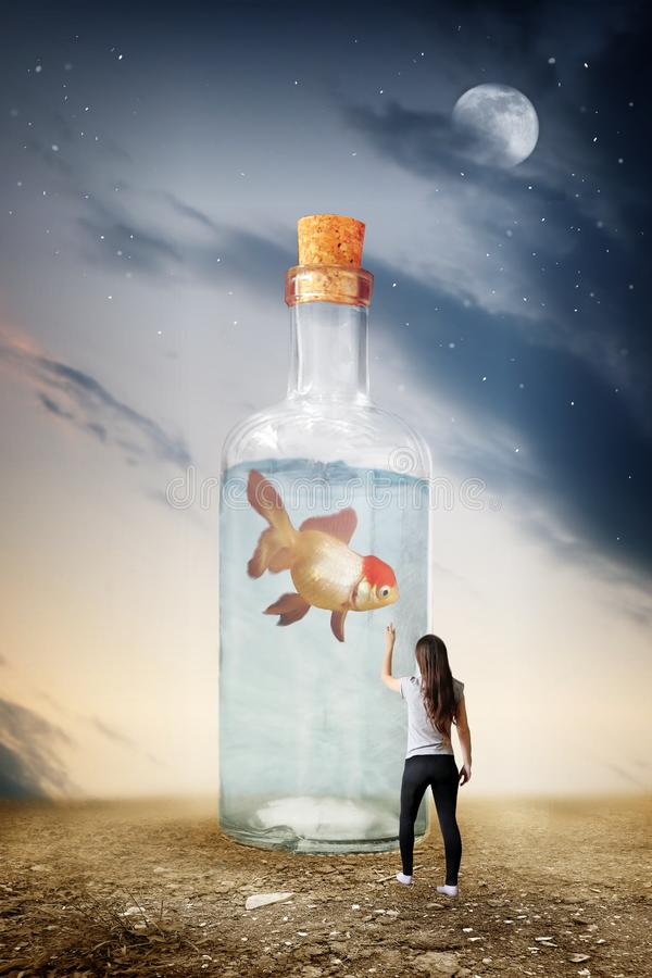 Surrealism of glass bottle with fish. Surrealism photo manipulation of glass bottle with fish royalty free stock photography