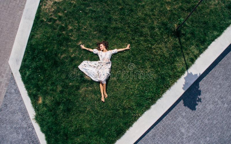 Surrealism. Happy red-haired girl lies barefoot on a green lawn in a dress. Aerial view. Surrealism. Happy red-haired girl lies barefoot in a dress on a green stock photos