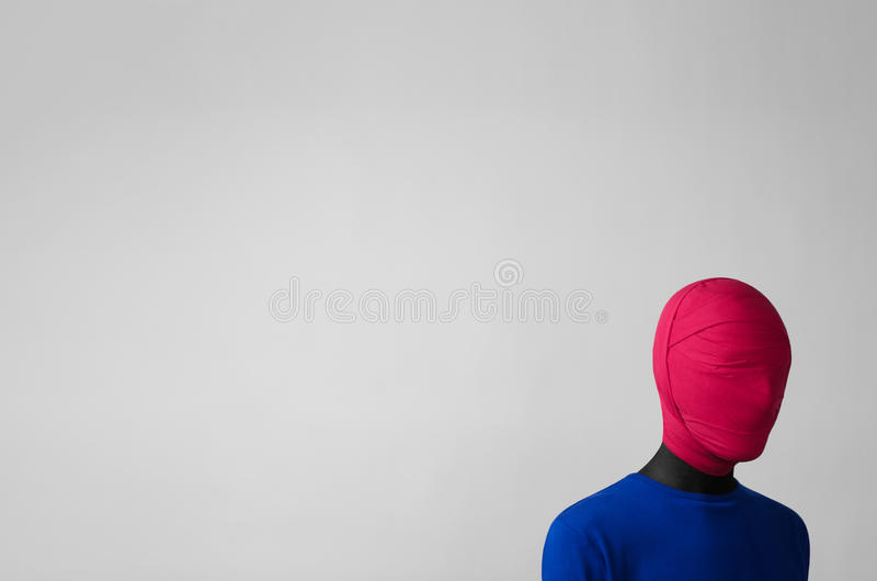 Surrealism. Theme: man in a blue jacket with a pink cloth tied around his head is in the corner on a gray background in studio royalty free stock image