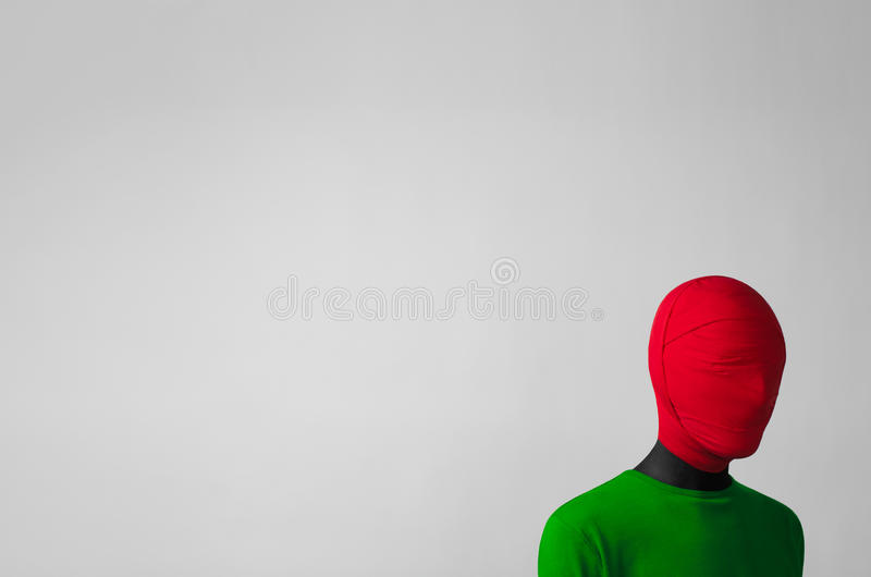 Surrealism. Theme: man in a green jacket with a red cloth tied around his head is in the corner on a gray background in studio stock images