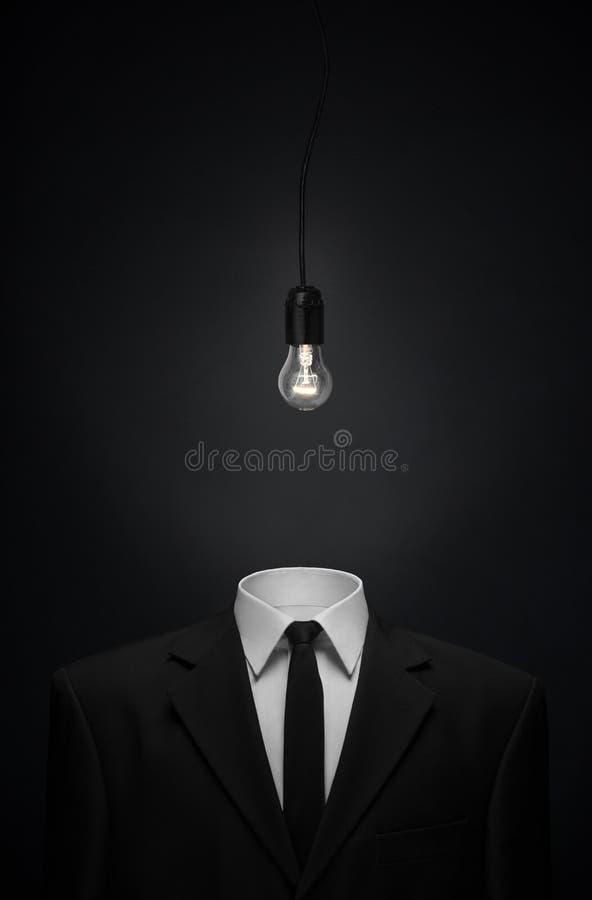 Surrealismus- und Geschäftsthema: Brennglasbirne anstelle eines Hauptmannes in einem schwarzen Anzug auf einem dunklen Hintergrun lizenzfreie stockfotografie