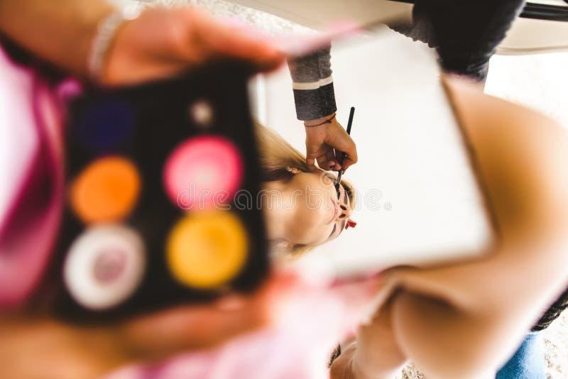 Surrealistisches Porträt junger Dame, die Make-up mit Spiegel machen lizenzfreie stockbilder