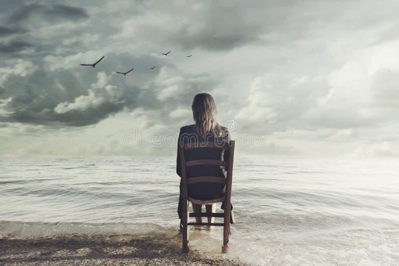 Surrealistyczni kobiet spojrzenia przy nieskończonym obsiadaniem na krześle wśrodku morza fotografia royalty free