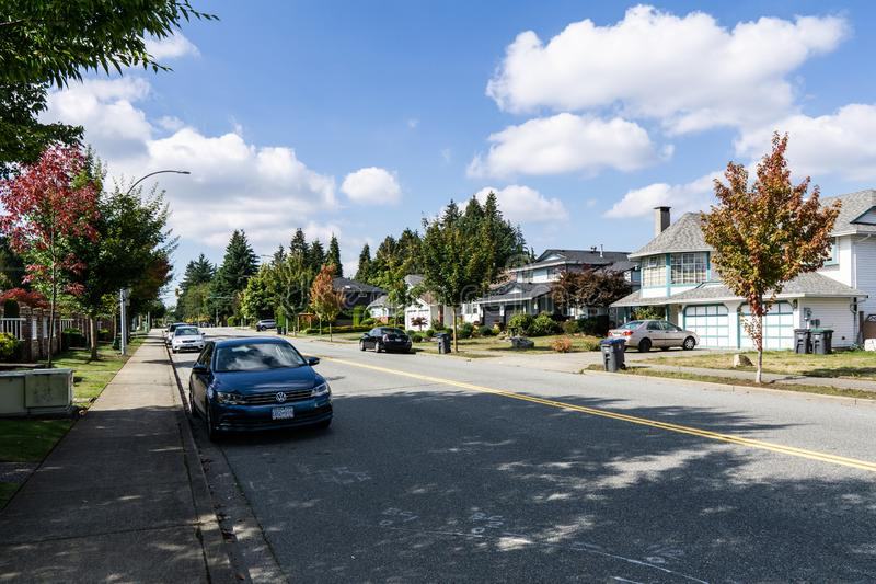 SURREY, CANADA - SEPTEMBER 19, 2018: city road in residential area with cars on a autumn sunny day. Fall, street, green, season, yellow, foliage, colorful royalty free stock images