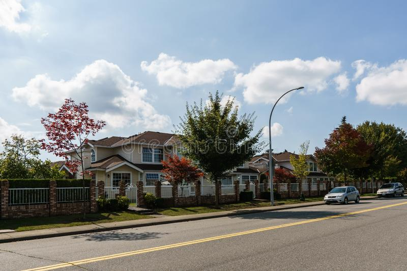 SURREY, CANADA - SEPTEMBER 19, 2018: city road in residential area with cars on a autumn sunny day. Fall, street, green, season, yellow, foliage, colorful royalty free stock photography