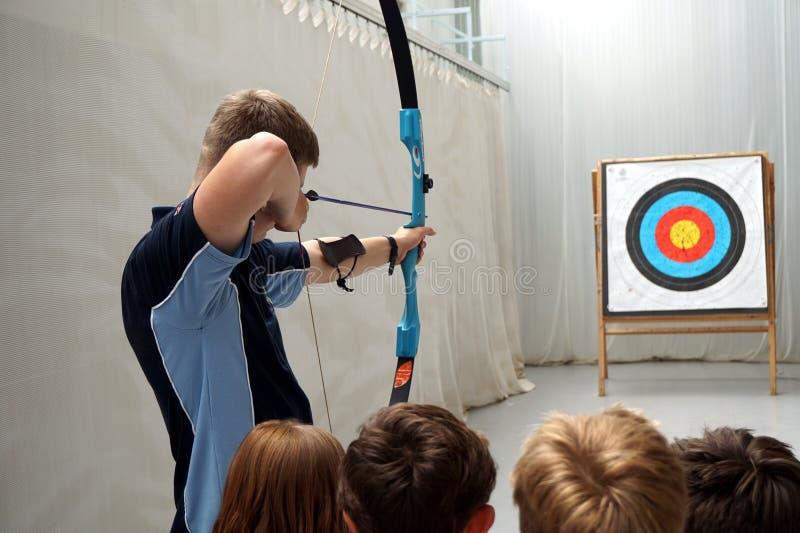 SURREY, ENGLAND, GROSSBRITANNIEN, AM 11. JUNI 2016: Bogenschießenlehrer zeigt vier Kindern, wie man den Bogen zielt stockfotos