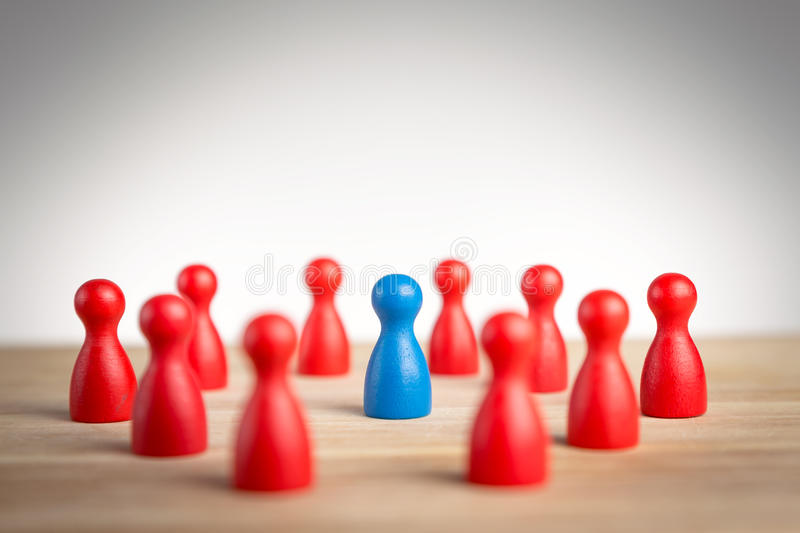 Surrounded by adversity or praised for being different concept. With figurines royalty free stock image
