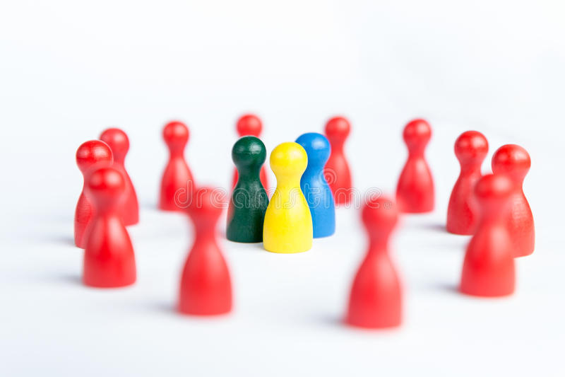 Surrounded by adversity or praised for being different concept w. Team surrounded by adversity or praised for being different concept with figurines royalty free stock photos