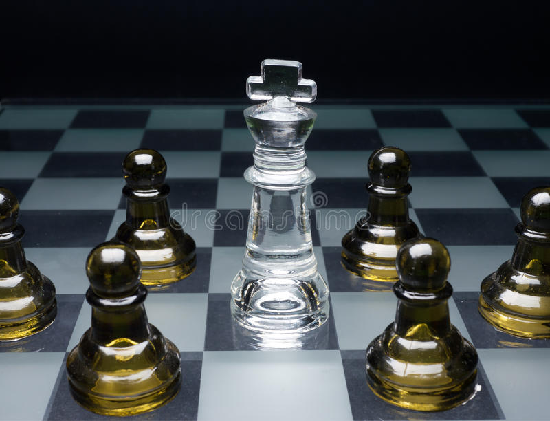 Surrounded, the games over. A white chess king surrounded by the enemy royalty free stock image