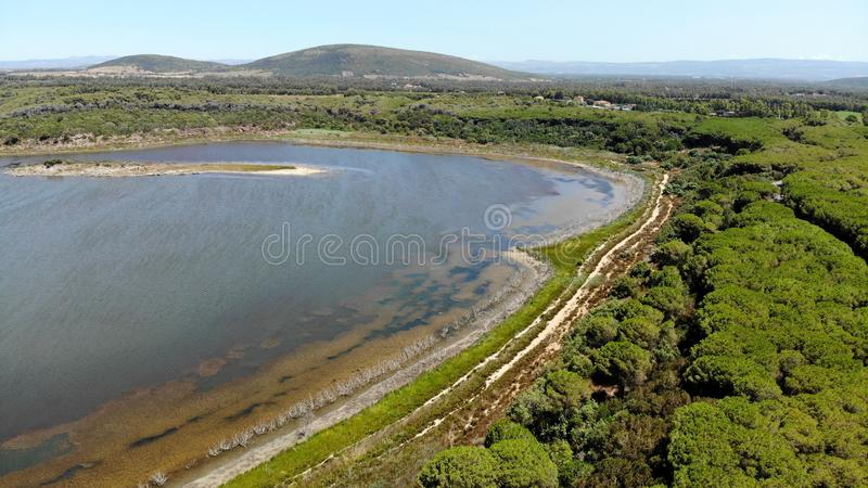 Aerial view by drone, Baratz kake, sardinia, Italy. Surrounded by low wooded hills, Lago Baratz is the only natural lake in Sardinia royalty free stock images