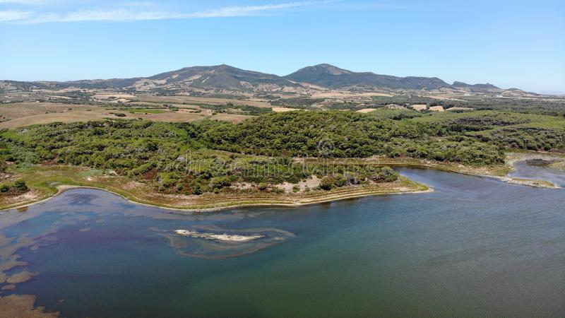 Aerial view by drone, Baratz lake, sardinia, Italy. Surrounded by low wooded hills, Lago Baratz is the only natural lake in Sardinia royalty free stock image
