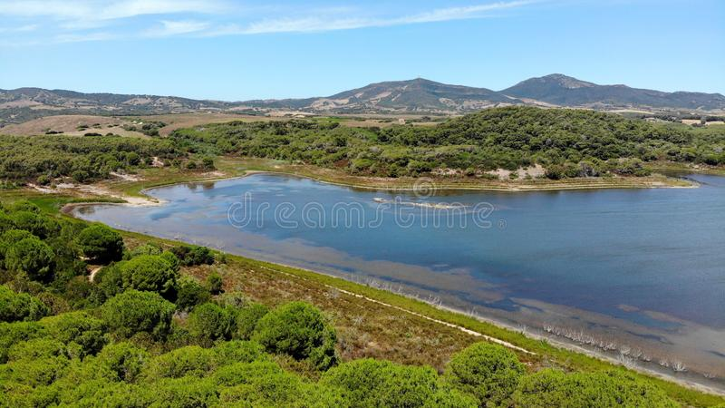 Aerial view by drone, Baratz lake, sardinia, Italy. Surrounded by low wooded hills, Lago Baratz is the only natural lake in Sardinia royalty free stock photography