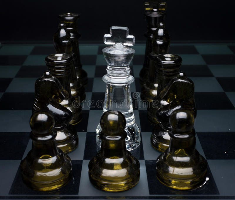 Surrounded - No Hope. A chess king surrounded by all members of the opposing enemy royalty free stock photos