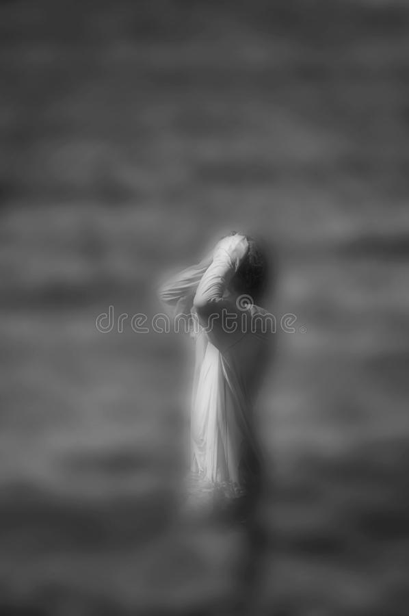 Surrreal image of woman standing in water. Surreal blurred black and white image of unrecognizable woman standing in water royalty free stock image