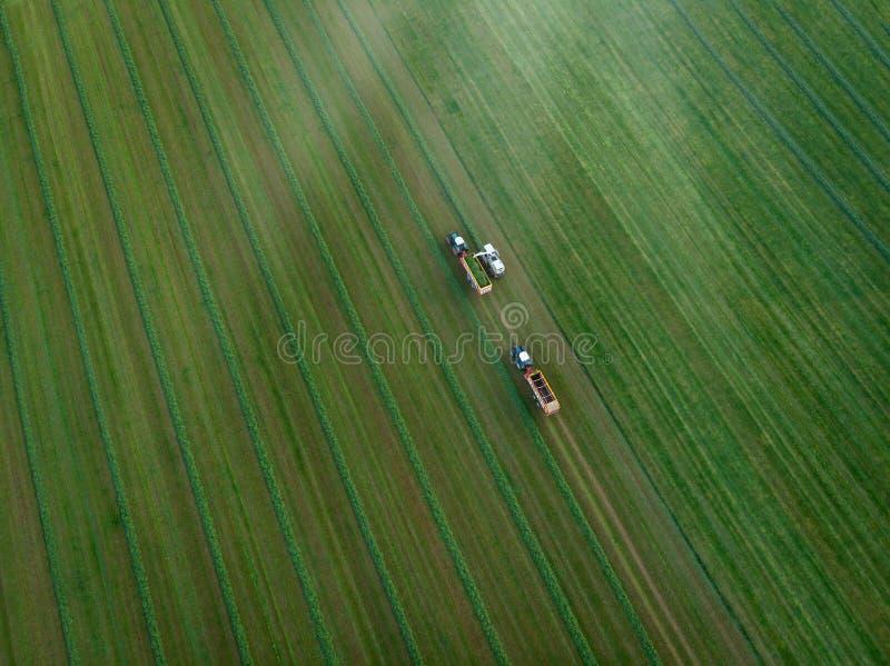 Surrskott av det jordbruks- fältet med traktorer som skördar hö royaltyfria foton