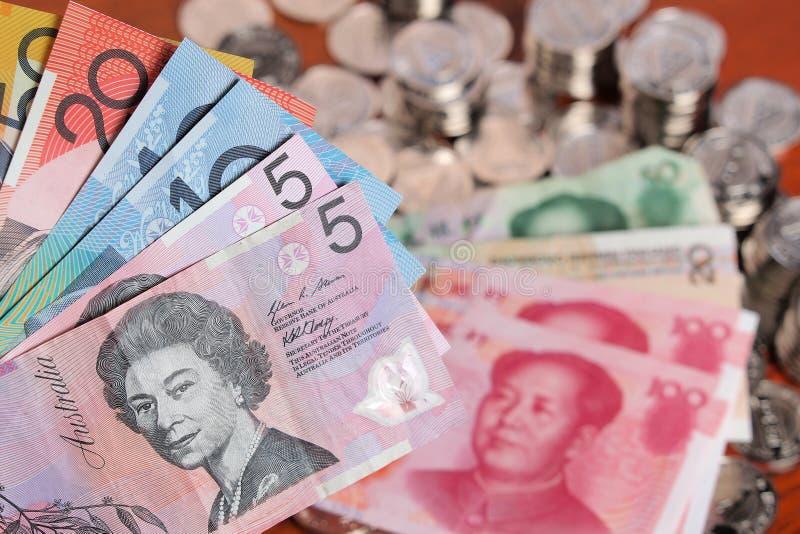 Surtido de billetes de banco del dólar australiano en frente de una pila de chino Yuan imagen de archivo libre de regalías