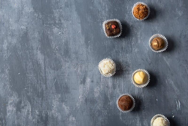 Surtido de caramelos de chocolate finos, de blanco, de oscuridad y de chocolate con leche en fondo gris Dulces fondo, visión supe fotografía de archivo