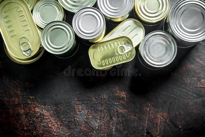 Surtido de diversas latas cerradas con la comida enlatada foto de archivo