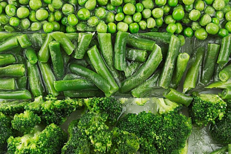 Surtido de guisantes verdes congelados frescos, habichuela verde, bróculi con el primer de la escarcha como fondo fotografía de archivo libre de regalías
