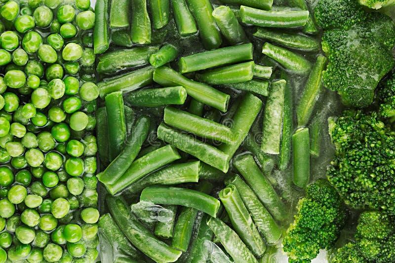 Surtido de guisantes verdes congelados frescos, habichuela verde, bróculi con el primer de la escarcha como fondo foto de archivo libre de regalías