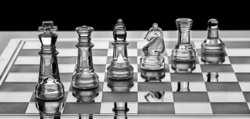 Surtido de pedazos de ajedrez de cristal en un tablero con blanco y negro foto de archivo