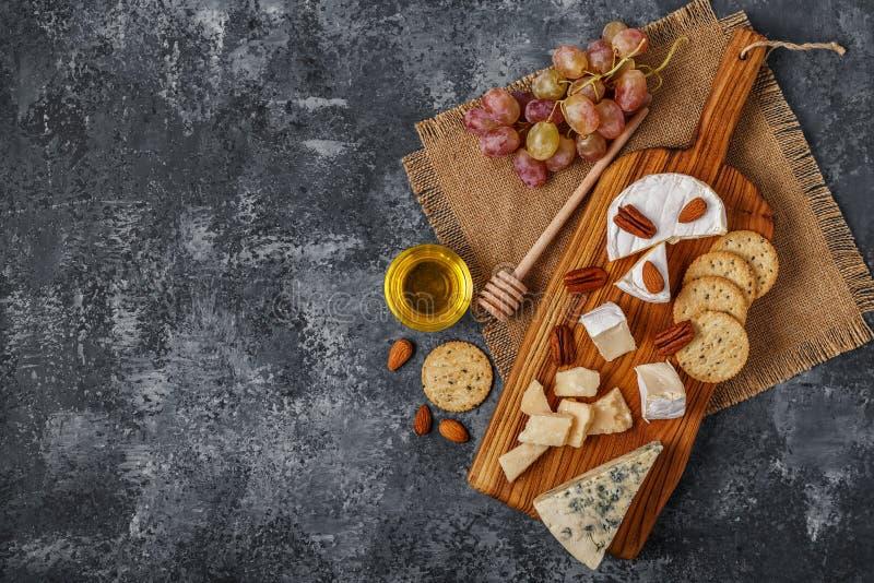Surtido de queso con la miel, las nueces y la uva en una boa del corte foto de archivo libre de regalías