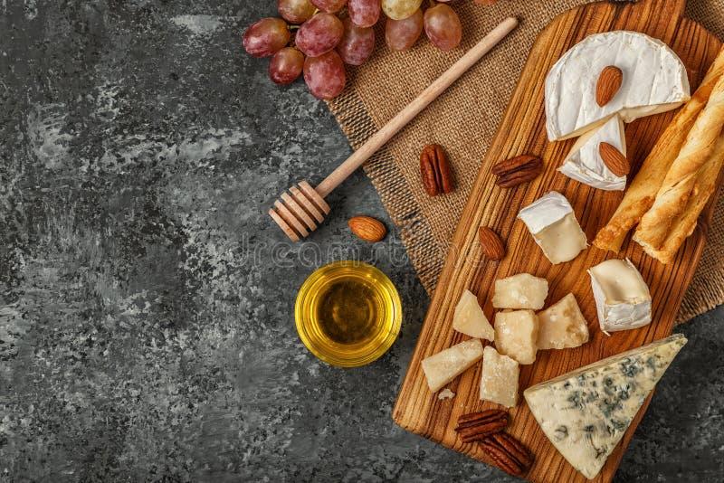 Surtido de queso con la miel, las nueces y la uva en una boa del corte foto de archivo