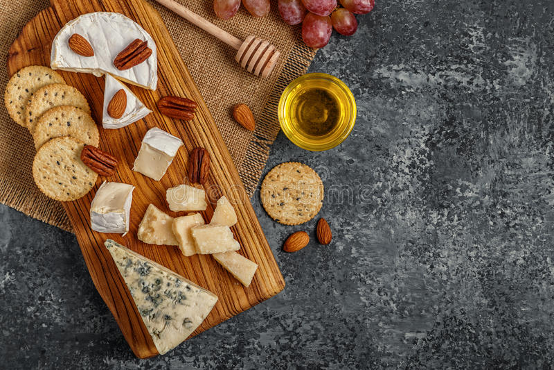Surtido de queso con la miel, las nueces y la uva en una boa del corte imagenes de archivo