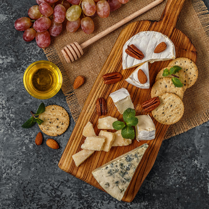 Surtido de queso con la miel, las nueces y la uva en una boa del corte fotos de archivo