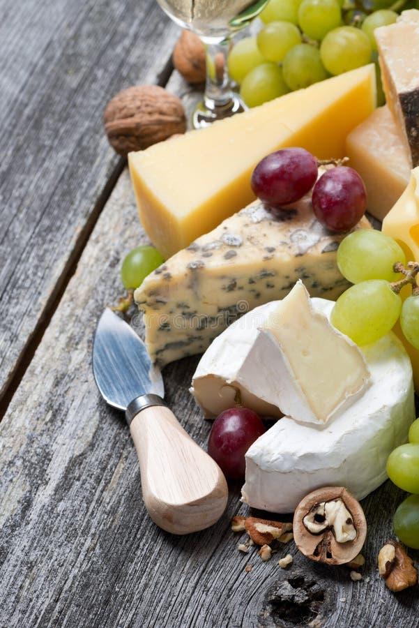 Surtido de quesos frescos, de uvas y de nueces en la tabla de madera imágenes de archivo libres de regalías