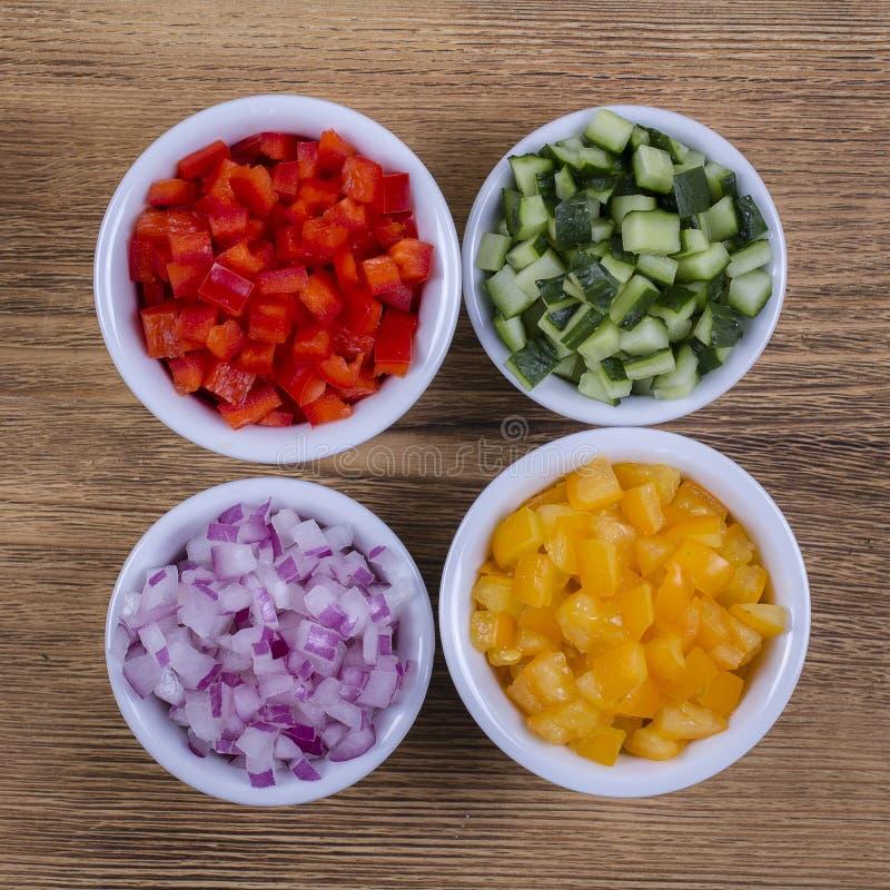 Surtido de verduras cortadas Pimientas, tomates, pepino y cebolla en cuencos fotografía de archivo libre de regalías