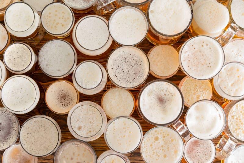 Surtido de vidrios de cerveza llenos, espumosos y de tamaños fotos de archivo libres de regalías