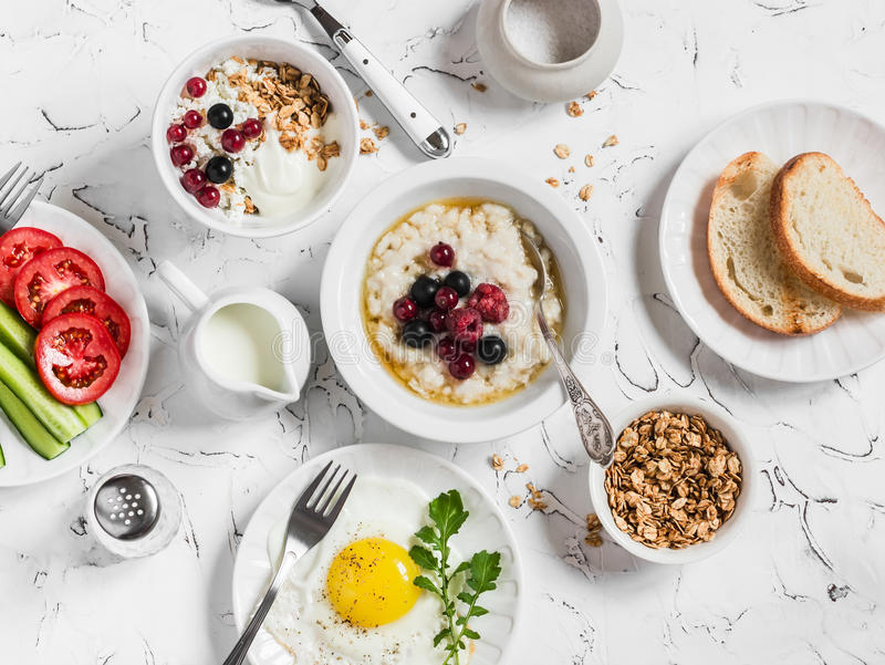 Surtido del desayuno - harina de avena con las bayas, el huevo frito, las verduras frescas, el requesón, el yogur y las bayas, gr fotos de archivo libres de regalías